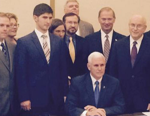 Gov. Pence signs the Religious Freedom law on Thursday in a private ceremony. the administration released photos of the event, but refused to identify who attended.